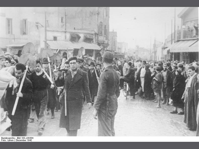 Kolonne mit jüdischen Zwangsarbeitern unter den Augen der muslimischen Bevölkerung in Tunesien im Dezember 1942. (Quelle: Bundesarchiv, Bild 183-J20384 / CC-BY-SA 3.0 /WikiCommons)